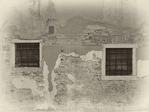 Sepiabild der Weinlese beunruhigten gemalten Wand mit zwei Fensterstangen mit weißen Einfassungen im hellen Sonnenlicht und im Sc stockbilder