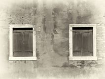 Sepiabild der Weinlese beunruhigten gemalten Wand mit zwei hölzernen Fensterläden geschlossenen Fenstern mit weißen Einfassungen  stockfoto
