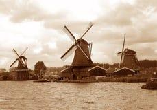 Sepiaton von drei niederländischen Windmühlen der Ufergegend unter dem bewölkten Himmel, die Niederlande stockfotografie
