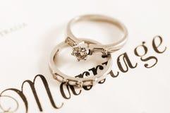 Sepiaweinleseretrostilhochzeits- und -diamantVerlobungsringe auf Heiratsurkunde Lizenzfreies Stockfoto