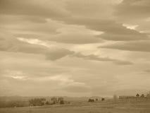 Sepiawolken über Feld Stockfotografie