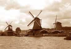 Sepiowy brzmienie trzy nabrzeże Holenderskiego wiatraczka pod chmurnym niebem, holandie fotografia stock