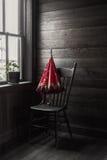 Sepiowy wizerunek czerwony parasolowy obsiadanie na krześle okno Fotografia Stock