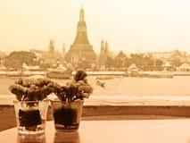 Seppia Tone Couple Vases dei fiori con Temple of Dawn nel fondo con colore morbido del fuoco filtrato usato come modello Immagine Stock