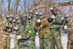 Amis dans les masques et le paintball de jeu de camouflage Photos stock