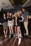 Sept amis focalisés se tenant et posant ensemble Photos libres de droits