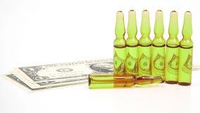 Sept ampoules en verre m?dicales pour l'injection sur le fond des billets de banque du dollar images libres de droits
