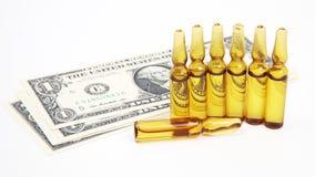 Sept ampoules en verre m?dicales pour l'injection sur le fond des billets de banque du dollar photo libre de droits