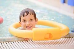 Sept années de garçon apprenant à nager à la piscine Images stock