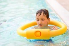 Sept années de garçon apprenant à nager à la piscine Image libre de droits