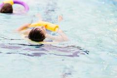 Sept années de garçon apprenant à nager à la piscine Photo libre de droits