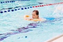 Sept années de garçon apprenant à nager à la piscine Images libres de droits