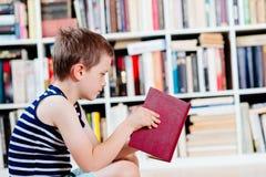 Sept années de garçon lisant un livre dans la bibliothèque Photographie stock