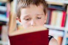 Sept années de garçon lisant un livre dans la bibliothèque Images libres de droits