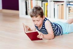Sept années de garçon lisant un livre dans la bibliothèque Photo stock