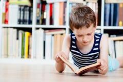 Sept années de garçon lisant un livre dans la bibliothèque Photos stock