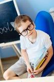 Sept années heureuses de garçon tenant ses fournitures scolaires Photo stock