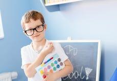 Sept années heureuses de garçon tenant ses fournitures scolaires Image stock
