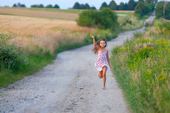 Sept années mignonnes de fille exécutant dans la route de filds Image stock