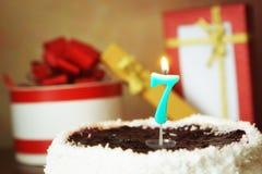 Sept ans d'anniversaire Gâteau avec la bougie et les cadeaux brûlants Photos libres de droits