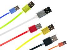 Sept câbles multicolores d'usb ont arrangé diagonalement sur un cadre, sur un fond d'isolement par blanc La famille unit futur te Image stock