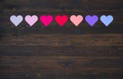 Sept coeurs dans diverses couleurs sur le fond en bois rustique de conseil Image libre de droits
