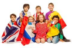 Sept enfants avec des drapeaux enveloppés dans différentes bannières Photographie stock