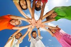 Sept enfants ont mis des bras dans la forme d'étoile Photo stock