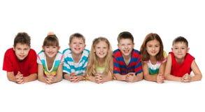 Sept enfants se trouvant sur l'étage Image stock