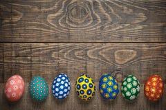 Sept oeufs de pâques colorés sur le concept en bois de fond Photographie stock libre de droits