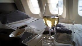 SEPTEMBER 2014: Äta middag för första klass som är onboard en Boeing 747, vitt vin, vatten och muttrar Royaltyfri Foto
