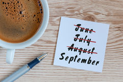 September beginning and summer end concept written at notepad with morning cup of coffee. Striked June, July, August Royalty Free Stock Photography