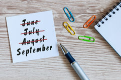 September beginning and summer end concept written at notepad on workplace background. Striked June, July, August Royalty Free Stock Photos
