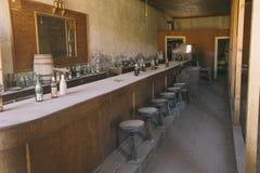 """12 september, 2014 Bodie Ghost town†""""Oude westelijke zaalbar met barstoelen en oude alcoholdrank Stock Foto"""