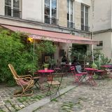 Petite Maison dans la Cour, Paris. September 2017: Cafe tables and chairs in a small cobbled courtyard in Paris royalty free stock photos