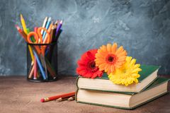 September 1 concept postcard, teachers day, back to school, supplies, alarm clock, daisies royalty free stock photo