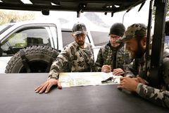 SEPTEMBER 16 2018 - DUBOIS, WY: Adult male hunters gather around. Adult male hunters gather around base camp, discussing and looking at a map of the local area royalty free stock image
