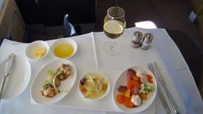 SEPTEMBER 2014: Eerste Klasse die aan boord van Boeing 747 dineren stock fotografie