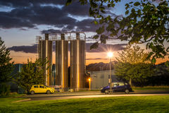 25 September, 2015, factory silos beyond workers car park at sunset Stock Photo