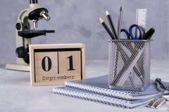 1 september Houten kalender, groep schoollevering op een grijze lijst Royalty-vrije Stock Foto's