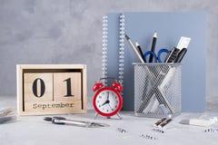 1 september Houten kalender, groep schoollevering, rode wekker op een grijze lijst Stock Afbeelding