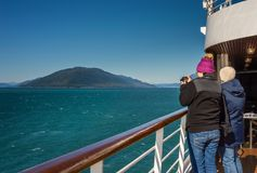 September 14, 2018 - Inside Passage, AK: Cruise travelers photographing scenery. September 14, 2018 - Inside Passage, Alaska: Cruise ship passengers aboard stock photos