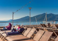 September 14, 2018 - Inside Passage, Alaska: Cruise passengers reading outdoors. September 14, 2018 - Inside Passage, Alaska: Passengers on Holland America`s royalty free stock photography