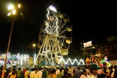 September 2017, Kolkata, Indien Besökare i en parkera på natten runt om ett jätte- hjul under durgpujaen 2017 på Deshapriya parke arkivfoto
