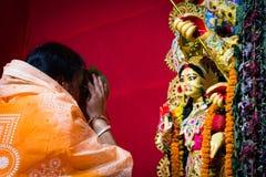 September 2017 Kolkata, Indien Dame, die ihr pranam und Hingabe durga Idol für die Segnung anbietet lizenzfreies stockfoto