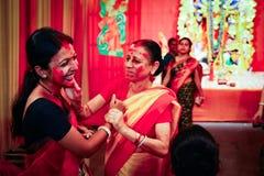 September 2017, Kolkata, Indien Två oidentifierade damer som spelar cinnoberfärgsindurkhela på dagen av dashamien arkivfoton