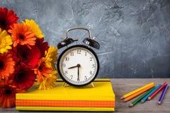 1. September Konzeptpostkarte, Lehrer ` Tag, zurück zu Schule oder College, Versorgungen, Wecker, ein Bündel von Gerbera Lizenzfreie Stockbilder