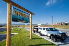 Welcome to Wyoming state border crossing sign, with a truck in the photo. LUSK, WYOMING: Welcome to Wyoming state border crossing welcome sign on a sunny day stock image