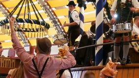 17 september, 2017 - München, Duitsland: Goed gekleed in nationale Beierse kostuums, spelen de mensen trommels en onderhouden men stock videobeelden
