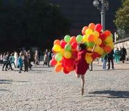September 2017, Moskou, Rusland Meisje in rode kleding met ballons Stock Afbeeldingen